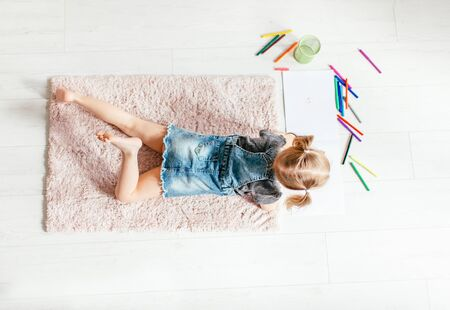 Top view of charming little girl drawing using colorful pencils while lying on the floor in her room at home.