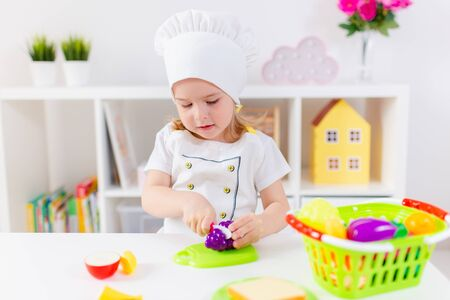 Little blonde girl in white cook uniform playing with toy fruits and vegetables at home, in kindergaten or preschool. Game activities to play with a child at home.