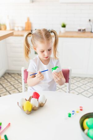 Happy little girl painting easter egg with watercolors sitting at the modern light kitchen.