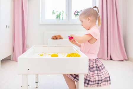 Little blonde girl playing with yellow magic sand on a white table in a light room. Sensory development. Lessons in a kindergarten