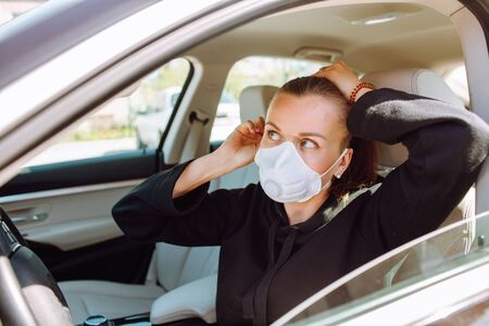 Woman with protective mask at her face and sitting in the car and brush her hair. Quarantine concept.