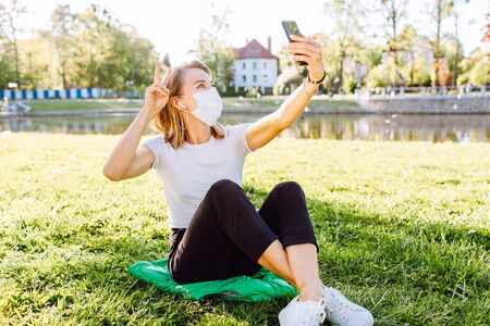 A white woman in face mask while using her phone for selfie and video chats. The new recommendation - everyone to wear masks in public during the coronavirus pandemic