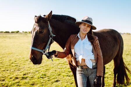 Beautiful young woman in a hat and gloves with a broun horse in a field on a sunset. Horseback riding Stok Fotoğraf