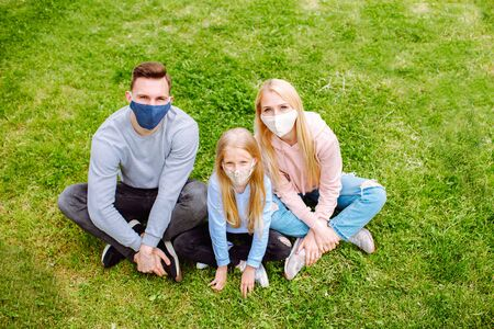 Family members sitting on a grass close each other, smiling in the camera wearing cloth face masks. Father, mother and daughter protect themselves from the virus