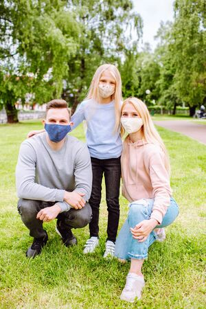 Family members embracing each other, smiling in the camera wearing cloth face masks. Father, mother and daughter protect themselves from the virus