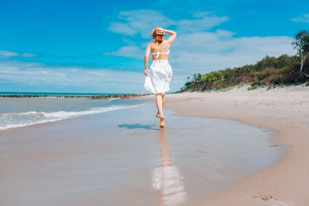 Beautiful woman wearing straw hat and white swimsuit and skirt walking along the surf line on beach near waves. Summer holidays in tropics. Sun protection