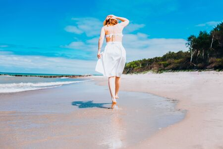 Beautiful sexy woman wearing straw hat, white swimsuit and skirt walking along the surf line on beach. Summer holidays in tropics. Copyspace. Sun protection Stockfoto