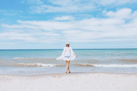 Beautiful woman wearing straw hat, white swimsuit and skirt walking along the surf line on beach. Summer holidays in tropics. Copyspace. Sun protection Stockfoto