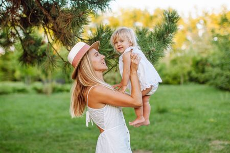 Family of little blonde girl and her middle age mother in the park in summer time. Childhood, single mother, age parents concept