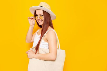 Young attractive woman in a white hat and white summer dress with eco shopping bag smiling on a yellow studio background 版權商用圖片 - 150251636