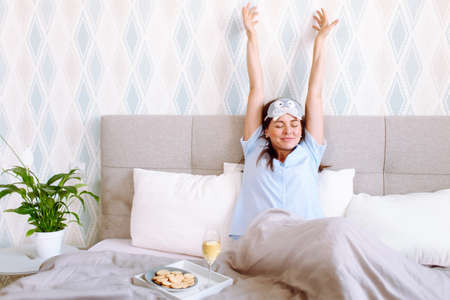 Young woman wearing blue pajanas and sleeping mask waking up happily after a good night sleep with her hands up.