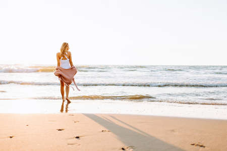 A young slim girl stands walking on the beach or ocean and look at the horizont. A woman dressed in a warm sweater. Toned 免版税图像
