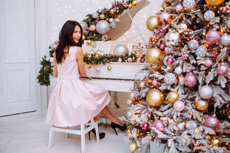 Merry Christmas and New Year. Cheerful womanl in white classic interior playing on a white piano against the background of a decorated Christmas tree.