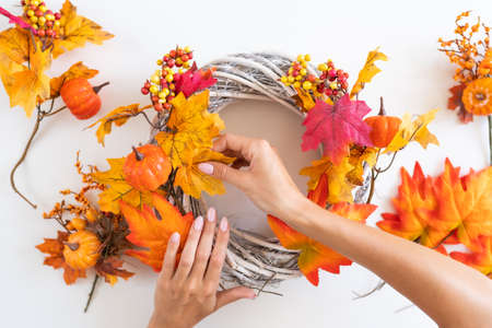 Florist at work: woman makes an autumn wreath at the door from yellow leaves, decorative pumpkins and berries. Top View