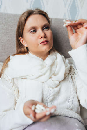 Young woman with a handful of pills lies in bed at home wearing sweater and a warm scarf and look at pill. Flu, cold, sickness. Banque d'images