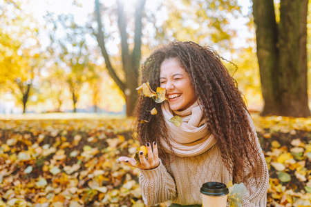 Positive afro hair woman with beautiful smile wearing knitted sweater and scarf throw yellow autumn leaves in park on sunny day