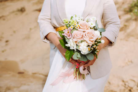 Anonymous bride with wedding bouquet close up at sandy beach