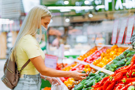 Young blonde woman wearing protective mask pick fresh vegetable on stall at market. Woman buying food