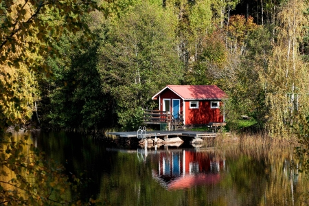 Typical Swedish red cottage at a small lake
