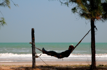 Dolphin Bay, Thailand - January 18, 2011: Fisherman taking a break in Dolphin Bay, Prachuap Khiri Khan, Thailand.