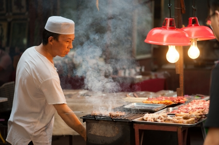 meat skewers: Xian, China – June 20, 2012: Hui man grills skewers at famous Muslim Street in Xian. Hui people are a muslim ethnic minority in Xian and run a lively market at Muslim Street. Editorial