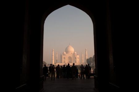 mumtaz: Agra, India - February 6, 2011: Tourists admire Taj Mahal from its entrance on an early morning. Taj Mahal ,regarded by many as the worlds most beautiful tomb, was built by Mughal emperor Shah Jahan in memory of his third wife, Mumtaz Mahal.