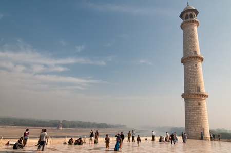Agra, India - February 6, 2011: Tourists admire one of the minarets of Taj Mahal. The minarets intentionally tilt slightly away from Taj Mahal tomb so that they will fall away from the tomb if they collapse.