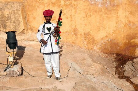 Jaipur, India - February 2, 2011: Rajasthani man posing with traditional instrument outside Amer Fort. Five thousand tourists visit the famous Amer Fort every day.