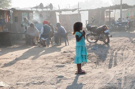 Rajasthan, India � February 3, 2011: Little girl in a blue dress and too large sandals watches traffic pass by her village on an early morning in Rajasthan.