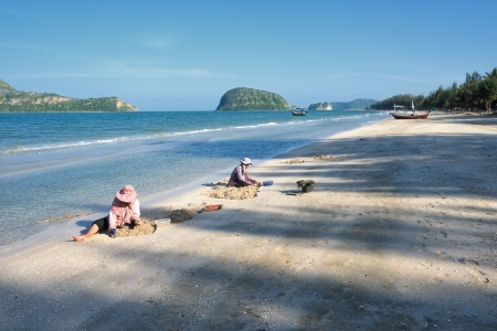 Dolphin Bay, Thailand - January 13, 2013: Two Thai women picking mussels at the beach in Dolphin Bay, Prachuap Khiri Khan, Thailand.