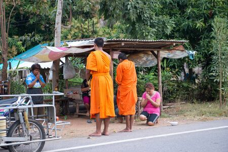 almsgiving: Hua Hin, Thailand - January 25, 2013: Thai women offering alms to two buddhist monks early in the morning in the countryside outside Hua Hin. Offering food is one of the oldest and most common rituals of Buddhism.