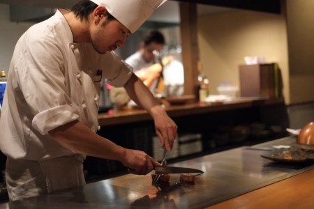 Kyoto, Japan - April 7, 2013: Japanese chef preparing Kobe beef at a restaurant in Kyoto.