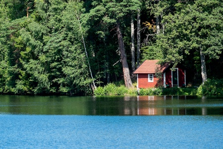 Summer in Sweden - a typical red little cottage by a lake photo