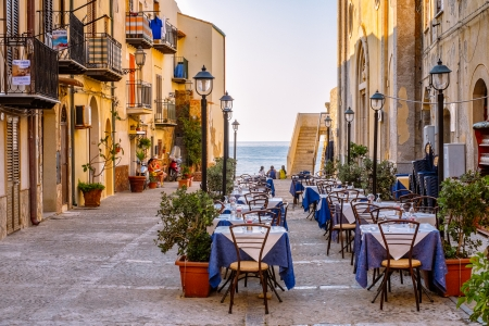 Cefalù, Sicily, Italy – July 17, 2013  A square with a trattoria  waiting for customers in the old town of Cefalù  Cefalù is one of the most popular destinations for a Sicilian vacation