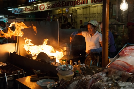 Hua Hin, Thailand � January 23, 2009  Thai boygirl chef woks a dish at the night market in Hua Hin  The famous night market in Hua Hin is a major tourist attraction