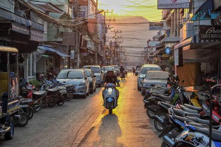 hin hua: Hua Hin, Thailand � January 21, 2013  A motorbike drives through a street at sunset in Hua Hin  Hua Hin is a major tourist destination in Thailand  Editorial