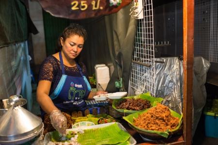 Hua Hin, Thailand 16 januari 2013 Thaise vrouw verkoopt straat eten op de avondmarkt in Hua Hin De beroemde avondmarkt in Hua Hin is een belangrijke toeristische attractie