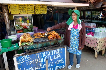 hin hua: Hua Hin, Thailand � March 2, 2013 Proud Thai woman displays grilled chicken in Khao Kalok south of Hua Hin  Hua Hin is a major tourist destination renown for it s food