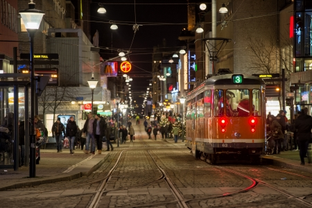 tramcar: Norrkoping, Sweden � December 20, 2013   A tram makes a stop at Drottninggatan during Christmas time in Norrkoping  Yellow trams are typical for Norrkoping, which is a historic industrial town   Editorial