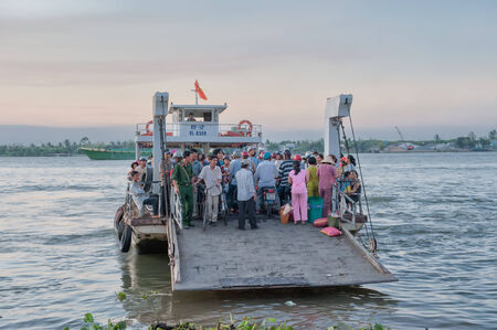 Vinh Long, Vietnam - March 6, 2009  A crowded ferry crosses one of the Mekong river tribituaries from Vinh Long to B�n Tre  The Mekong river is a major route for transportation in Southeast Asia