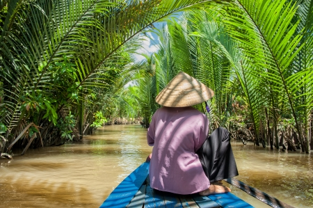 conical hat: Ben Tre, Vietnam - March 6, 2009  Vietnamese woman paddling a traditional boat in the Mekong delta at Ben Tre island  The Mekong river is a major route for transportation in Southeast Asia