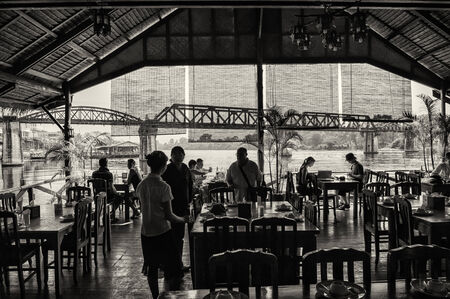 Kanchanaburi, Thailand � February 2, 2009  Tourists enjoy a lunch break nearby the bridge on the river Kwai in Kanchanaburi  The bridge is famous due to a movie and its history in WW2