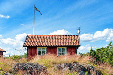 fishing cabin: Harstena, Sweden - July 22, 2009  Traditional red little cabin at Harstena Island in the Baltic Sea  Harstena belongs to the archipelago of Gryt and is a popular tourist destination