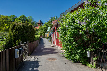 belongs: Sigtuna, Sweden – June 2, 2014  Idyllic narrow street in Sigtuna  Founded in 980 Sigtuna is the oldest city in Sweden and a popular tourist destination  Sigtuna belongs to Stockhom County and the province of Uppland  Editorial