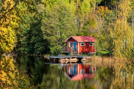 スウェーデン - 10 月の湖で伝統的な赤い小さな小屋の秋