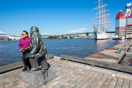 gothenburg: Gothenburg, Sweden - September 4, 2014: Asian tourist poses with the statue of poet Evert Taube.  Gothenburg is the second largest city in Sweden and an important harbor. Editorial