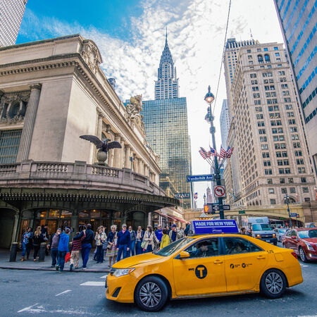 New York City, NY, USA - April 25, 2014: Yellow cab turns at the corner of Vanderbilt Avenue and E 42nd Street. This is the site of Grand Central Terminal which is the largest railway station with regard to number of platforms and tracks. Редакционное