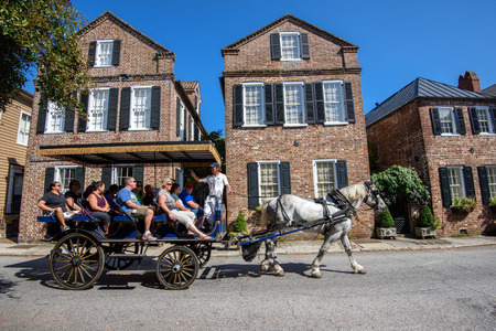 Charleston, SC, USA - October 13, 2014: Horse carriage with tourists enjoying the facades of Societe Francaise and historic traditional residential architecture in Charleston, SC.