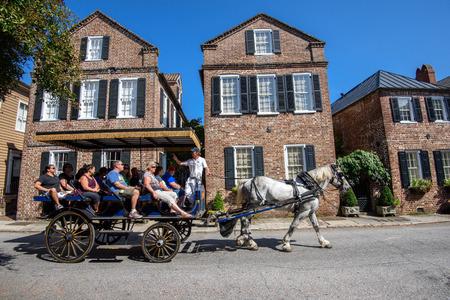 Charleston, SC, Verenigde Staten - 13 oktober 2014: Paard en wagen met toeristen genieten van de gevels van Societe Francaise en historische traditionele residentiële architectuur in Charleston, SC.