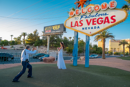 WEDDING DAY: Las Vegas, USA - October 7, 2014: A bride is photographed by the groom at the Welcome to Fabulous Las Vegas sign on the southern part of Las Vegas Boulevard. This iconic sign attracts crowds of tourists to have their photo taken here.